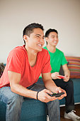 Young men playing video game on couch