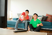 Young men playing video game with racing controller