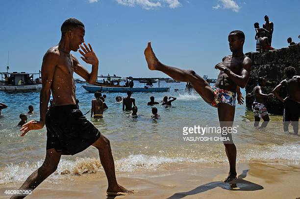 Young men practice Capoeira a Brazilian martial art at Boa Viagem beach in Salvador Bahía Brazil on January 1 2015 AFP PHOTO / YASUYOSHI CHIBA
