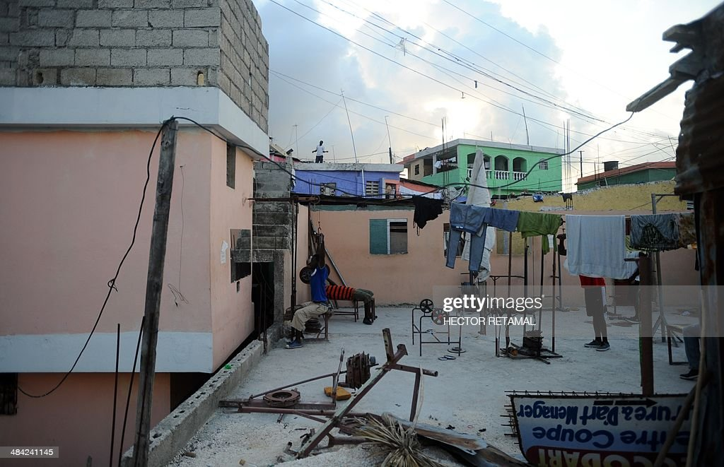 Young men practice weightlifting at a gym in the Jalousie neighborhood of Petionville, a suburb of Port-au-Prince on April 11, 2014. AFP PHOTO/Hector RETAMAL