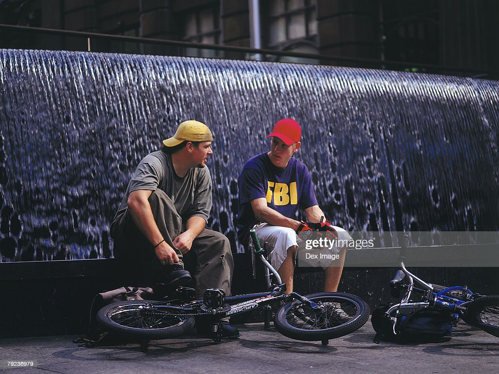 Young men resting on BMX on water fountain : Stock Photo