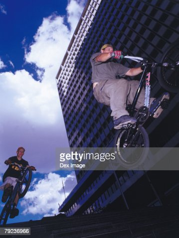 Young men riding BMX down stairs : Stock Photo