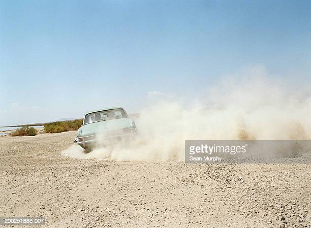 Young men riding in car, making dust cloud on dirt road