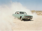 Young men riding in car on dirt road, dust cloud
