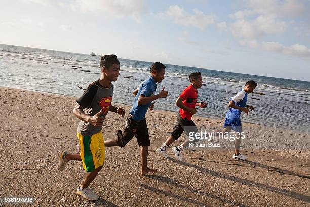 Young men running along the beach in Dili Timor Leste Timor Leste has a very young population and many young men train and keep fit After lots of...