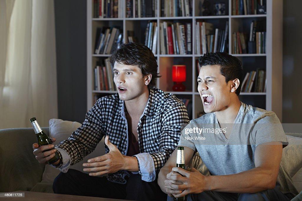 Young men shouting at tv, holding beer bottles