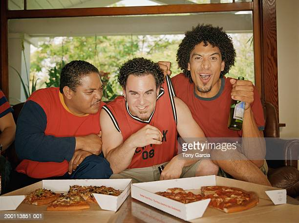Young men sitting in living room, eating pizza and beer