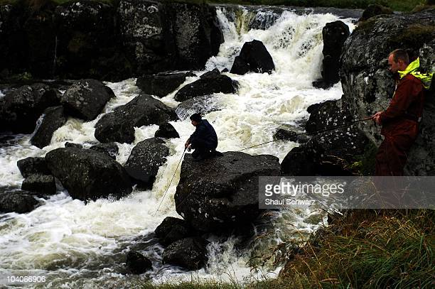 Young men stand on rocks as they try to fish in a small river as it flows in to the sea in the Faroe Islands July 30 2007 Although the economy of the...