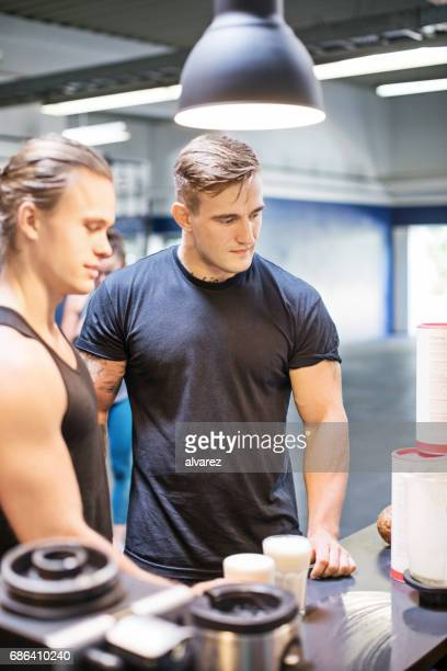 Young men standing at cafe in gym