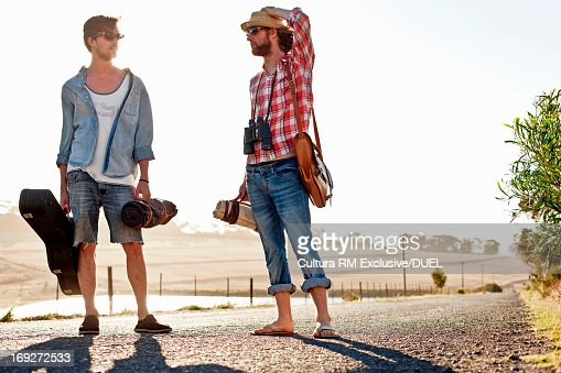 Young men standing together in sunlit road