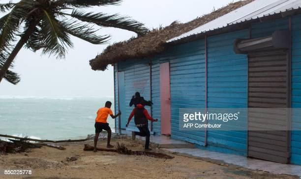 Young men take cover as winds lash the coastal city of Punta Cana in the Dominican Republic the eastermost tip of the La Espanola island it shares...