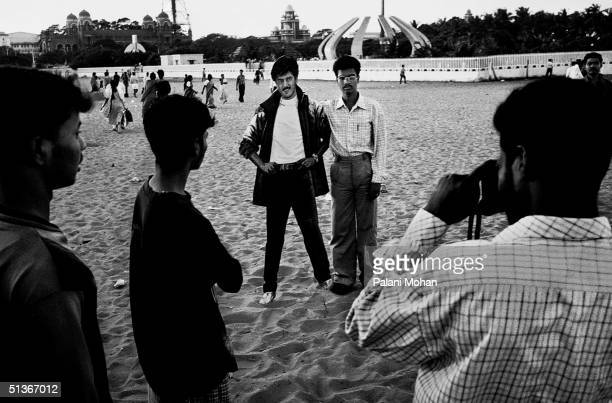 Young men take photographers of each other next to life sizes cardboard cut outs of famous Indian move stars on Marina Beach in December 2002 in...