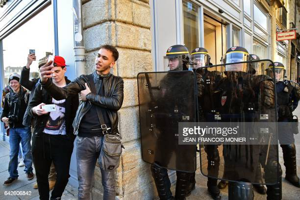 TOPSHOT Young men take provocative selfie photos as antiriot police officers stand guard during a demonstration against police brutality on February...