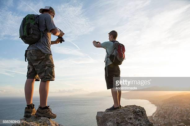 Jeune homme prendre et regardez des photos en haut de randonnée