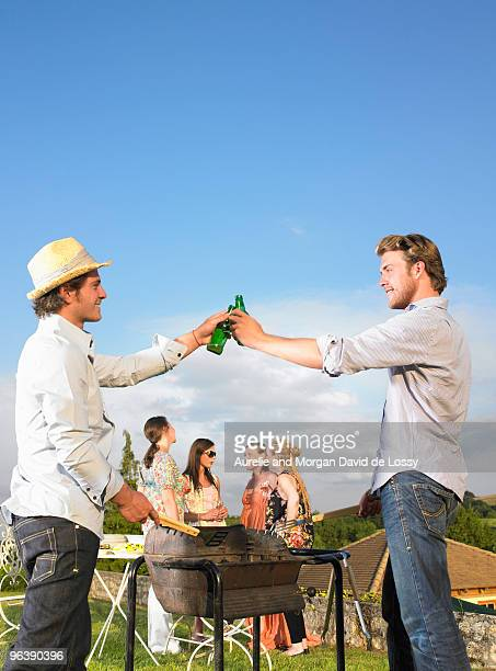 young men tending barbecue