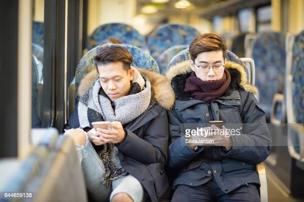 young men traveling with train using cellphone