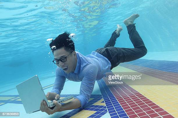 Young men use computers under water