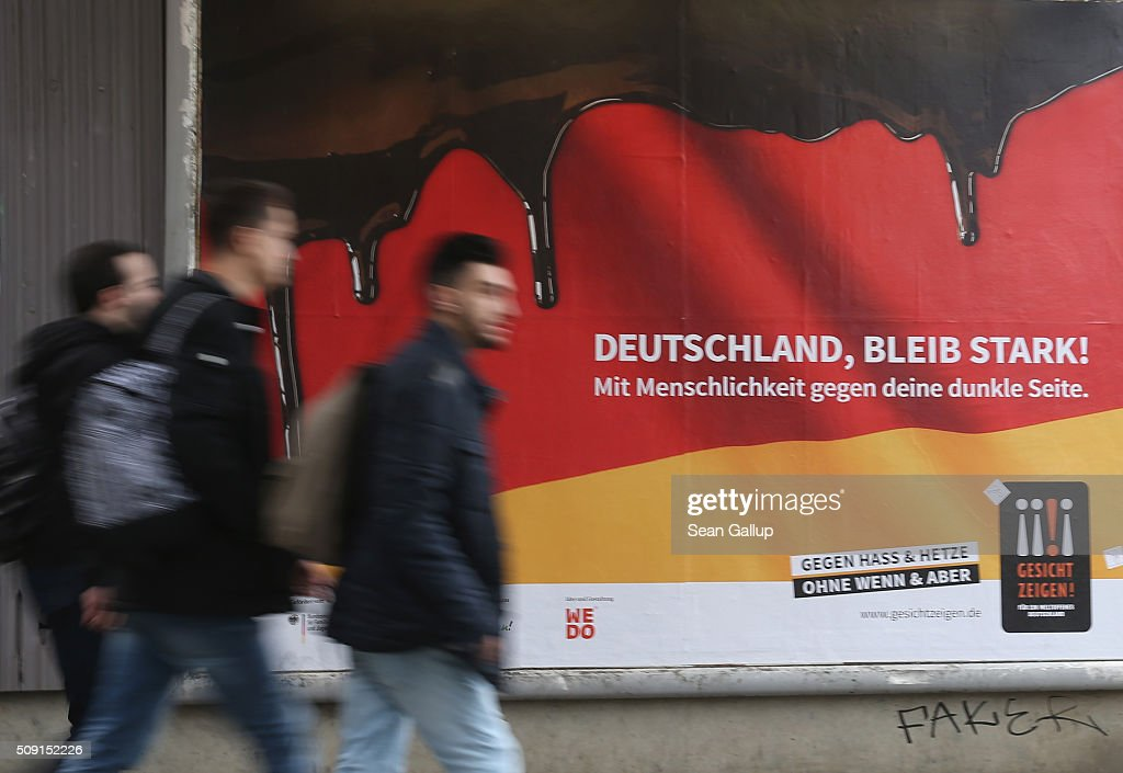 Young men walk past a poster showing the German flag with a dripping black portion and that reads: 'Germany, stay strong! With humanity against your dark side,' and below: 'Against hate and baiting, no if and but' on February 9, 2016 in Berlin, Germany. The poster is part of a campaign supported by Germany's Ministry for Families, Seniors, Women and Youth in an effort to encourage more tolerance, particularly of the 1.1 million migrants and refugees that arrived in Germany in 2015. Though a majority of Germans have shown a strong willingness to accept the newcomers and thousands have volunteered to help them, the country has also seen a growing number of attacks, including beatings, arson, vandalism and other violence against refugees and refugee shelters.