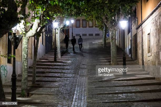 Young men walking on Cuesta de Carvajal cobbled street in Salamanca Spain