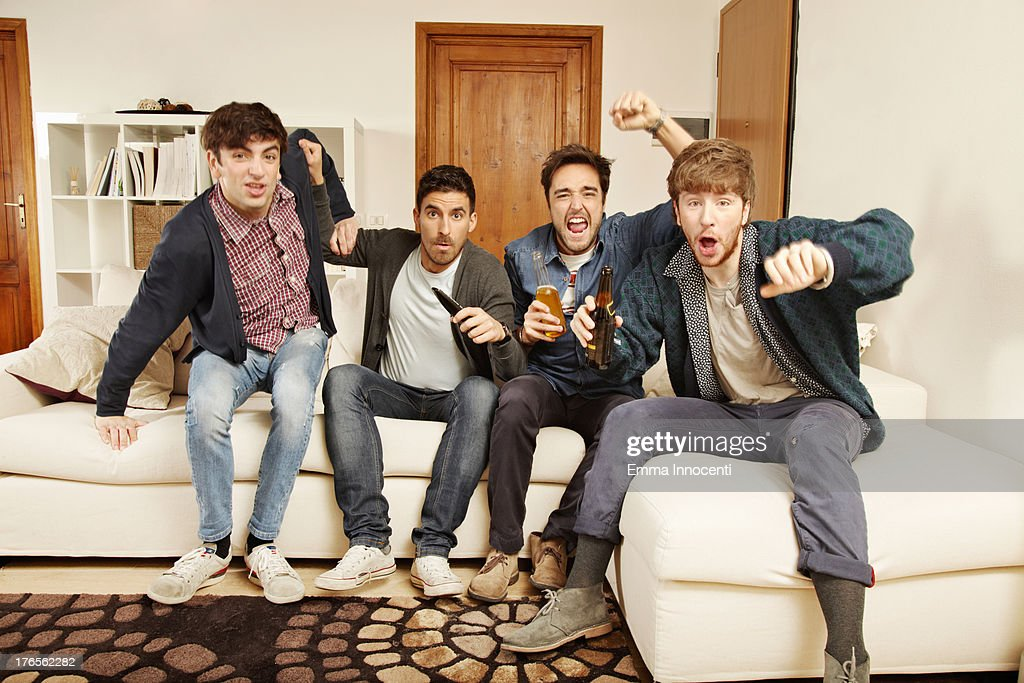 Young men watching tv indoors exulting : Stock Photo