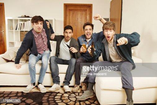 Young men watching tv indoors exulting