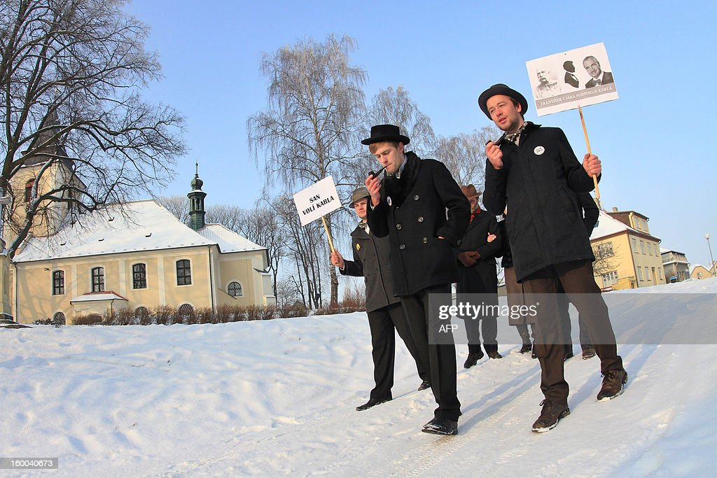 Young men wearing hat and bow tie, smoke a pipe as they hold a banner that reads 'Vote Karel Schwarzenberg' in the village of Sebranice, Czech Republic on January 25, 2013, day of the second round of the first direct Czech presidential election. Sebranice is a village that is known for its the traditional crafts and customs of the pre-war period. Czechs went to the polls to choose a new president between a former communist and a 75-year-old aristocrat whose Sex Pistols-inspired campaign brought the election to life and down to the wire.