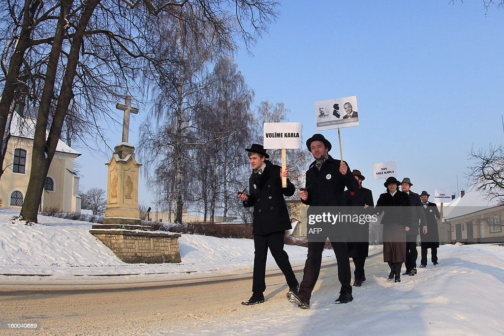 Young men wearing hat and bow tie, smoke a pipe as they hold a banner that reads 'Vote Karel Schwarzenberg' in the village of Sebranice, Czech Republic on January 25, 2013, day of the second round of the first direct Czech presidential election. Sebranice is a village that is known for its the traditional crafts and customs of the pre-war period. Czechs went to the polls to choose a new president between a former communist and a 75-year-old aristocrat whose Sex Pistols-inspired campaign brought the election to life and down to the wire. AFP PHOTO / RADEK MICA