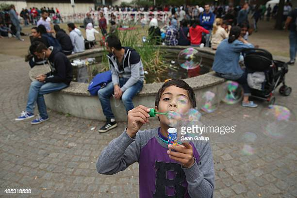 A young migrant boy from Syria blows soap bubbles as other migrants seeking asylum in Germany wait to register at the Central Registration Office for...