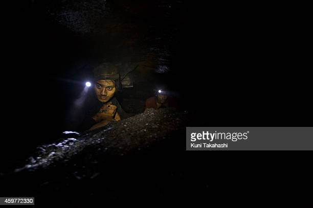 A young migrant coal miner from Nepal walks through a narrow hole at a coal mine in Jaintia Hills Meghalaya in India on April 29 2014 Indian...