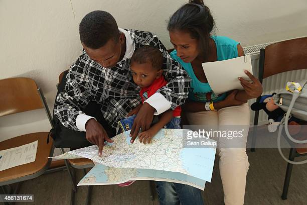 A young migrant couple from Eritrea look on a map of Europe as they prepare to depart with their son after they completed the registration process at...
