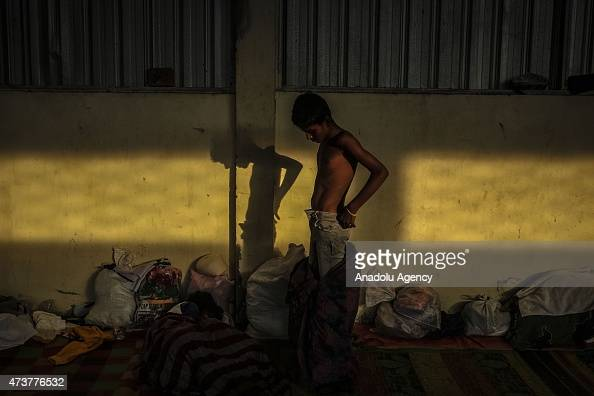 A young migrant from Myanmar changes his clothes at camp shelters at the confinement area in the fishing port of Kuala Langsa in Aceh province May 17...