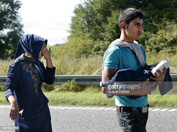 Young migrant holding a baby walks at the E45 freeway from Padborg on the DanishGerman border heading north to try to get to Sweden on September 9...