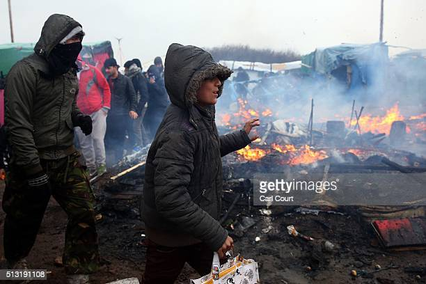 A young migrant walks past a burning hut as police and demolition workers clear part of the 'jungle' migrant camp on March 01 2016 in Calais France...