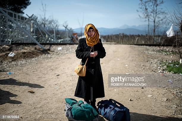 TOPSHOT A young migrant woman from Syria stands with her bags after crossing the GreekMacedonian border near the town of Gevgelija on February 23...