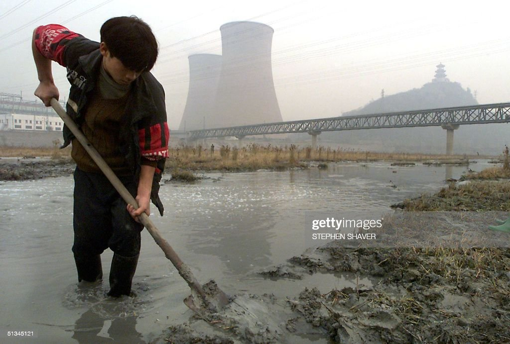A young migrant worker shovels heavily polluted mud and water from an almost dried up river bed to form a small diversion in the stream 10 November 1999 next to a massive power plant in Beijing. China is one of the worst polluted countries in the world, with its environment, especially its air and water quality, greatly suffering from decades of rampant, unchecked development with little regard given to the eventual health and environmental consequences. (ELECTRONIC IMAGE) AFP PHOTO/Stephen SHAVER