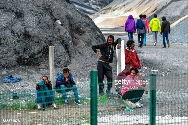 TOPSHOT Young migrants gather and wait on a mound on August 16 2017 in Calais The Lille court demanded that the migrants who decide to seek asylum in...