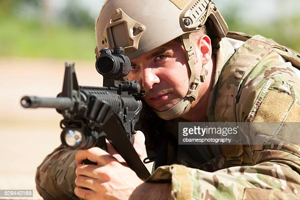 young military army soldier looks into gun sight and aims