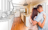 Young Military Couple Looking Inside Custom Kitchen and Design Drawing and Photo Combination.
