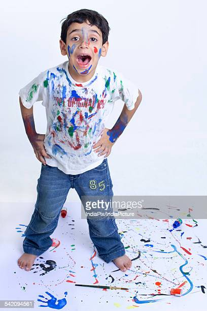 Young mischievous boy shouting with paint all over him against white background
