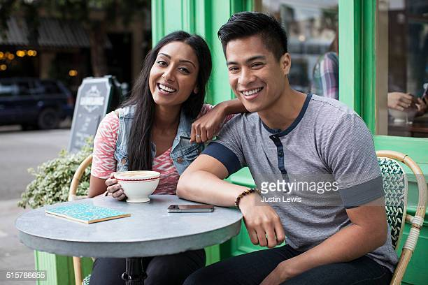 Young mixed race couple at cafe smiling at caemra