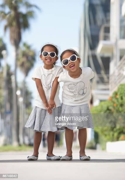 Young mixed race girls wearing sunglasses