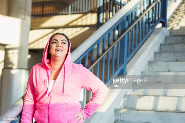Young mixed race Hispanic woman in pink hoodie