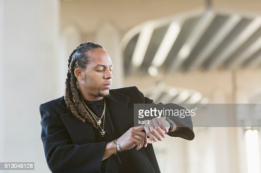 Young mixed race man in black coat looking at watch