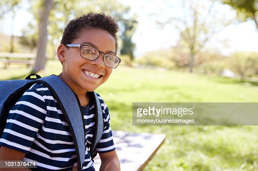 Young mixed race schoolboy in glasses smiling to camera : Stock Photo