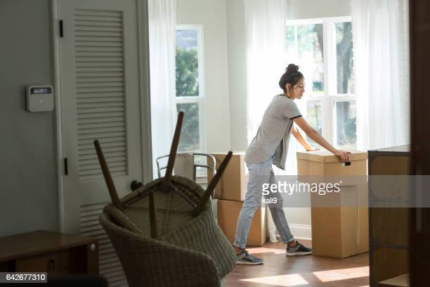 Young mixed race woman moving into new home