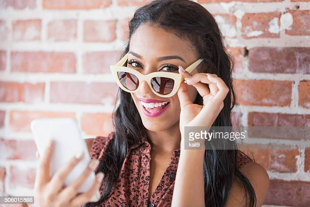 Young mixed race woman with mobile phone and sunglasses