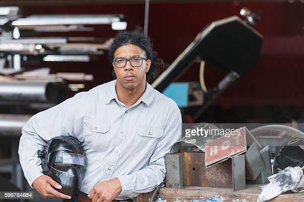 Young mixed race worker holding welders mask