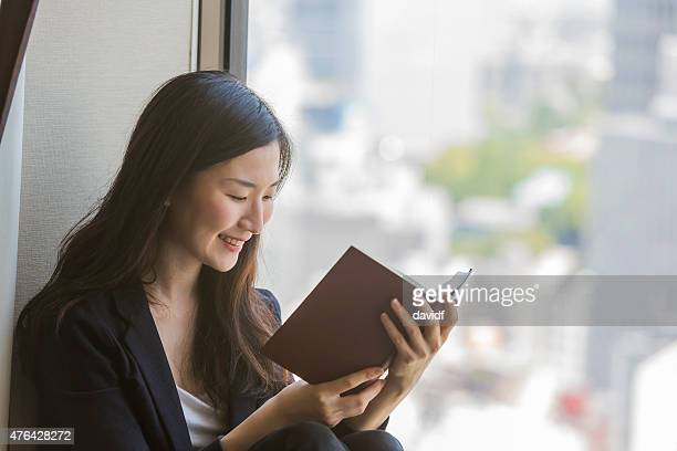 Young modern Japanese woman sitting reading a book