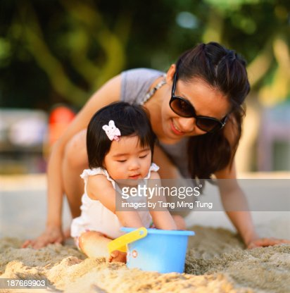 Young mom and baby playing on beach : Stock Photo