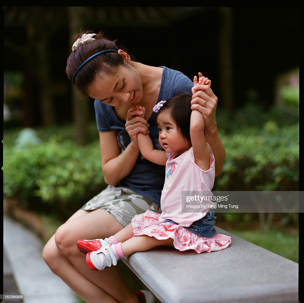 young mom and baby sitting and playing on bench : Stock Photo